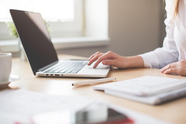 woman's hand on apple laptop track pad on desk
