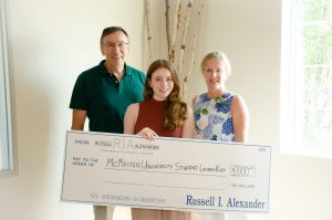 student and her parents holding scholarship cheque