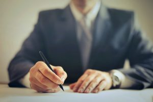 crop-businessman-signing-contract-in-office